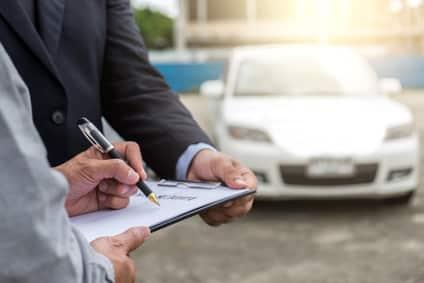 Zwei Männer ermitteln den Autowert auf einem Blatt Papier.