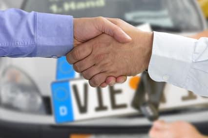 Schüttelnde Hände vor einem Auto.